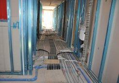 Die haustechnischen Verrohrungen von der Staubsaugeranlage, Hydraulik bis Elektrik bedecken den Boden.