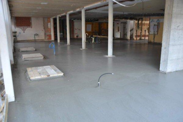 Der frische Unterbeton bedeckt nun alle Bodenleitungen.